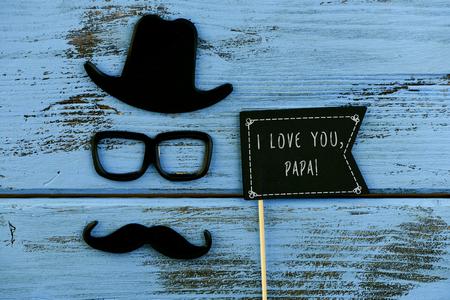 een zwarte vlag-vormig bord met de tekst Ik hou van je papa, en een snor, een bril en een hoed die het gezicht van een man op een blauwe rustieke houten oppervlak Stockfoto