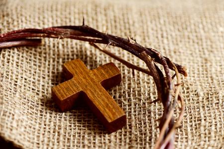 religion catolica: una pequeña cruz de madera y una representación de la corona de espinas de Jesucristo en un fondo de tela de arpillera Foto de archivo