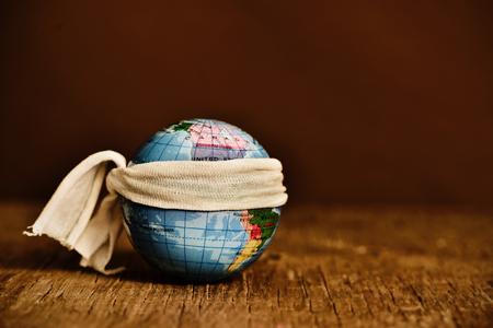 un trozo de tela atada alrededor de un globo terrestre, colocado sobre una superficie de madera rústica, con un efecto dramático