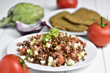 closeup of a white ceramic plate with refreshing lentil salad, on a white table with some raw vegetables