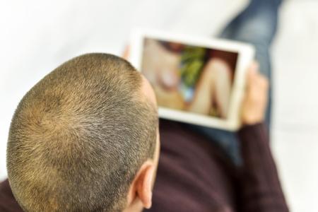 ソファの上に横たわる若い白人男彼のタブレット コンピューターのポルノを時計します。 写真素材