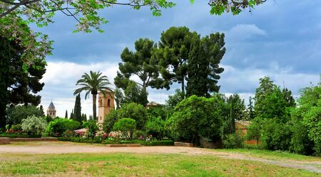 garden city: a view of the Gardens of La Alhambra in Granada, Spain, with the Convent of San Francisco in the background