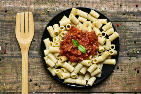 bolognese sauce: high angle shot of a wooden fork and a black plate with penne rigate with bolognese sauce on a rustic wooden table