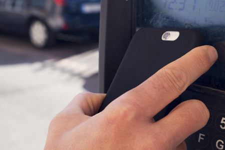 contactless: closeup of a young caucasian man using his smartphone to pay via contactless in a parking meter Stock Photo