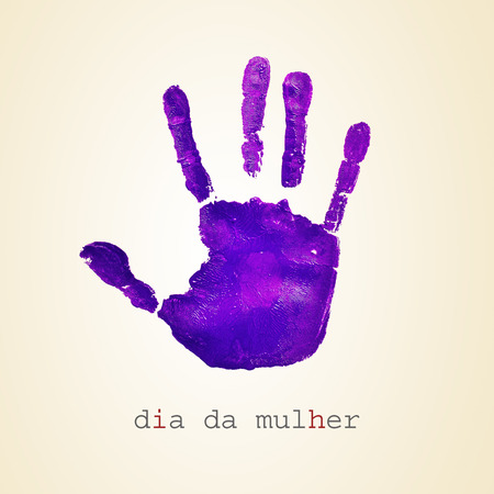 observance: a violet handprint and the text dia da mulher, womens day in portuguese, on a beige background