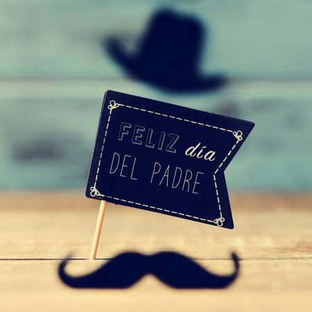 fun day: a black flag-shaped signboard with the text feliz dia del padre, happy fathers day in spanish, and a mustache and a hat forming the face of a man on a wooden surface