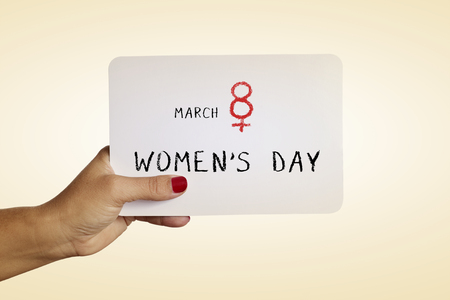 egalitarianism: the hand of a young woman with red polished nails holds a signboard with the text march 8 womens day, with the number eight as the female gender symbol Stock Photo