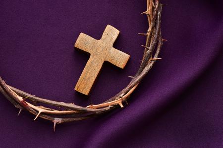 resurrección: tiro alto ángulo de una cruz cristiana de madera y la corona de espinas de Jesucristo en una pañería púrpura