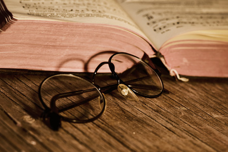 prose: closeup of a pair of retro round-framed eyeglasses and an open old book on a rustic wooden table, with a filter effect Stock Photo
