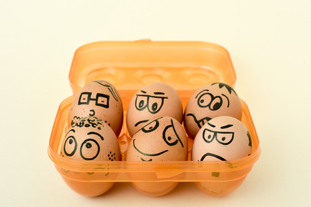 decorated: a pile of brown eggs ornamented with funny faces in an orange egg box, on an off-white background