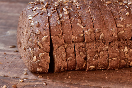 wholemeal: closeup of a sliced loaf of rye bread topped with sunflower seeds on a rustic wooden surface
