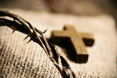 een klein houten kruis en een voorstelling van de doornenkroon van Jezus Christus op een jute doek achtergrond