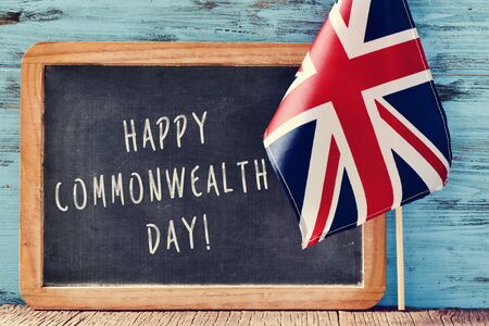 realms: a chalkboard with the text happy commonwealth day written in it and the Union Flag, on a wooden surface, against a blue rustic wooden background Stock Photo