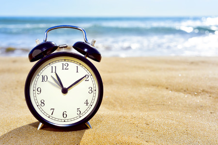 ahorros: Primer plano de un reloj de alarma en la arena de una playa que ajusta el adelantan una hora al comienzo de la temporada de verano