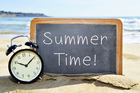 an alarm clock and a chalkboard with the text summer time on the sand of a beach Stock Photo