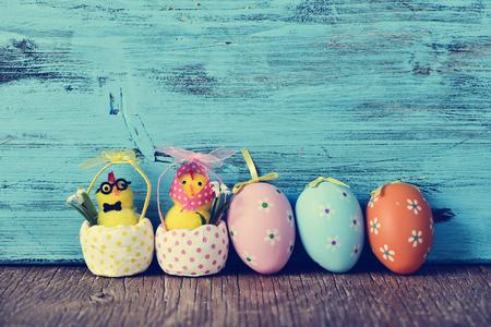 pollitos: un par de divertidos pollitos de peluche, un macho y una hembra, y algunos diferentes huevos de Pascua adornados en una superficie de madera, sobre un fondo azul de madera rústica