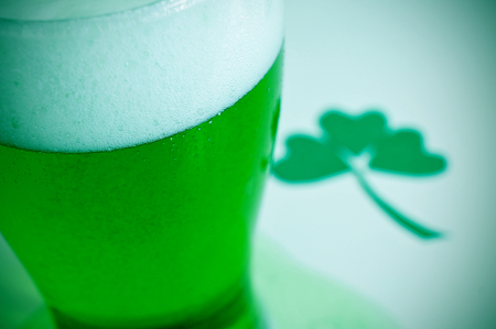 three leaved: closeup of a glass with dyed green beer and a three-leaved shamrock in the background, for saint patricks day Stock Photo