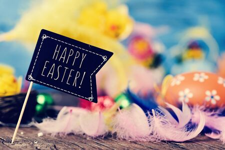 decorated eggs: closeup of a black flag-shaped signboard with the text happy easter on a wooden surface full of feathers of different colors and some decorated eggs Stock Photo