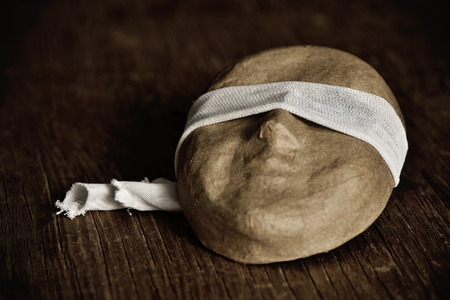 dictatorial: a paper-mache mask with a piece of fabric around its eyes, placed on a rustic wooden surface Stock Photo