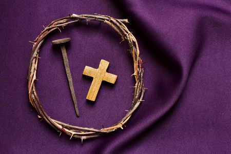 wooden cross: high-angle shot of a wooden christian cross, a rusty nail and the crown of thorns of Jesus Christ, on a purple drapery