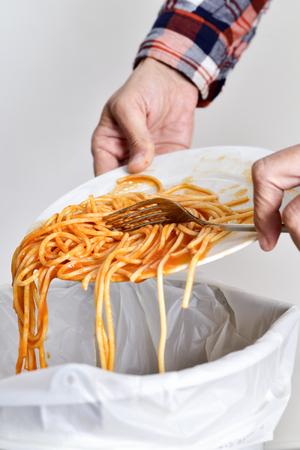 cesto basura: primer plano de un joven lanzando los restos de un plato de espaguetis a la papelera Foto de archivo