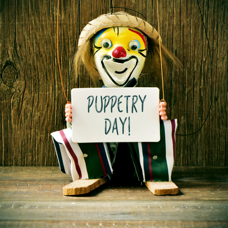 puppetry: closeup of an old marionette with its face painted as a clown holding a signboard with the text puppetry day Stock Photo