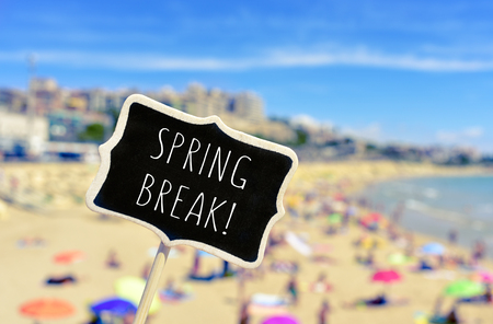 spring break: closeup of a black signboard with the text spring break written in it, in front of a blurred beach with many people bathing and sunbathing