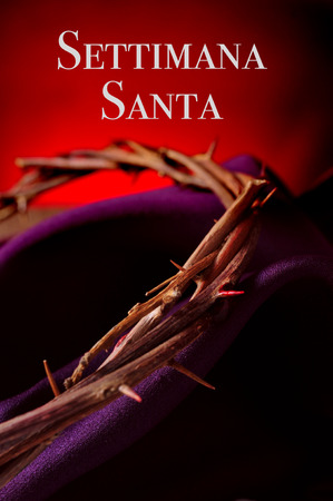 holy week: closeup of the crown of thorns of Jesus Christ on a purple fabric, and the text settimana santa, holy week in italian, against a red background Stock Photo