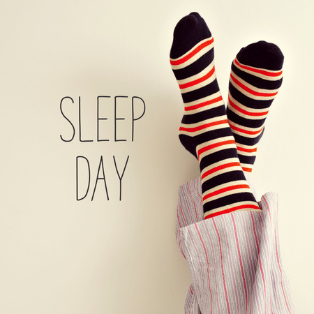 comfort: closeup of a young man in pajamas wearing colorful striped socks with his feet against the wall and the text sleep day