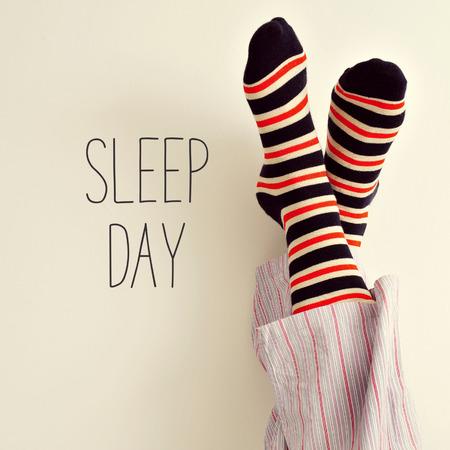 pies masculinos: primer plano de un hombre joven en pijama calcetines a rayas de colores con los pies contra la pared y al día el texto del sueño