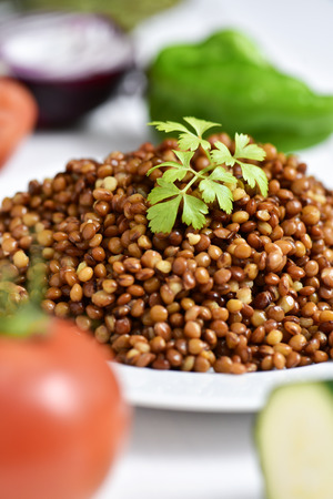 red cooked: closeup of a plate with cooked lentils on a white table with some raw vegetables, such as tomato, green pepper or red onion Stock Photo