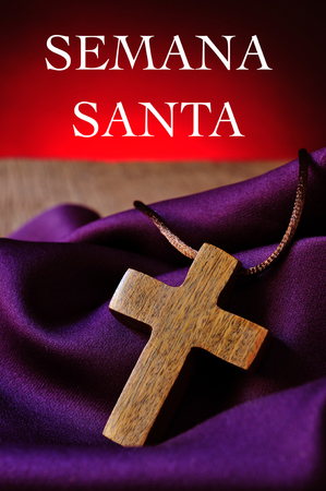 crucify: closeup of a small wooden cross on a purple fabric, and the text semana santa, holy week in spanish, against a red background