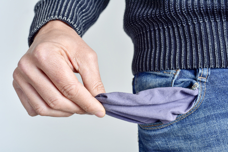 a broke young caucasian man in jeans showing his empty pocket