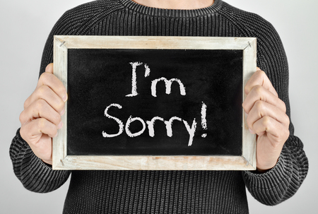 apologise: a young caucasian man shows a chalkboard with the text I am sorry written in it Stock Photo