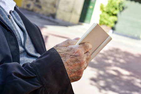 ageing: closeup of an old caucasian man reading a book outdoors