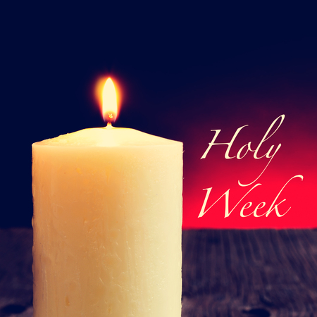 holy week: closeup of a lit candle on a rustic wooden surface and the text holy week