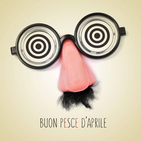 mope: fake eyeglasses, nose and mustache and the sentence buon pesce d aprile, happy april fools day written in italian in a beige background, with a retro effect Stock Photo