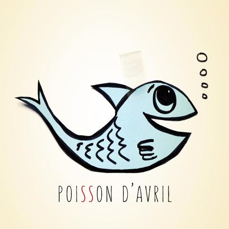 attach: un papel hecho a mano pescado azul atado con cinta adhesiva y el texto de Poisson d avril, día de los inocentes en francés Foto de archivo