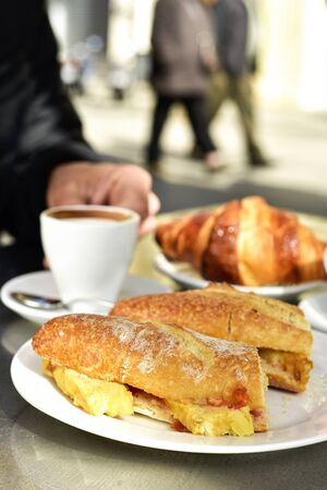 omelet: man sitting in a table in the terrace of a cafe set for breakfast, with some cups of coffee, a croissant and a spanish omelette sandwich Stock Photo