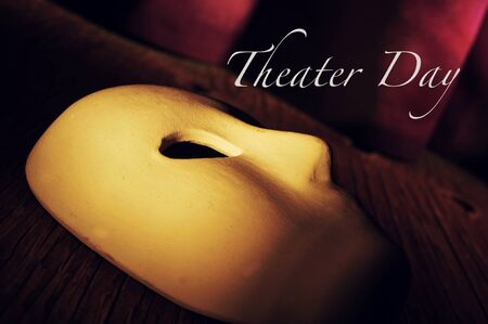 dramatic characters: a classical theatrical mask on a stage with an elegant act curtain in the background and the text theater day Stock Photo