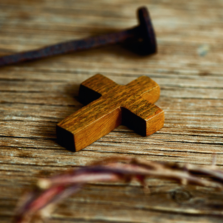 jesus: closeup of a small wooden cross, a depiction of the crown of thorns of Jesus Christ and a nail on a wooden surface
