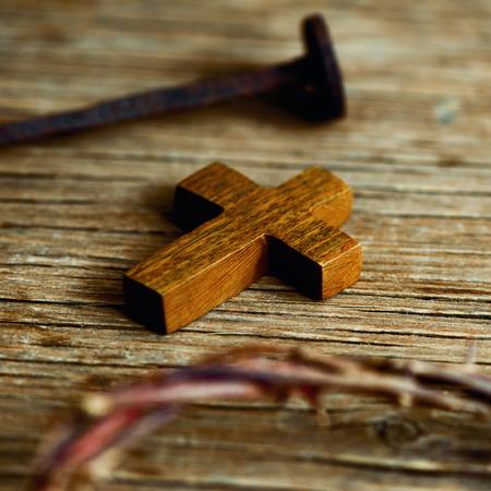 corona de espinas: primer plano de una pequeña cruz de madera, una representación de la corona de espinas de Jesucristo y un clavo en una superficie de madera Foto de archivo