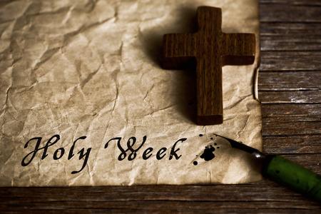 close-up van een kleine houten christelijk kruis, een oude kroontjespen en een gelige papier met de tekst heilige week geschreven met zwarte inkt in het, op een rustieke houten tafel