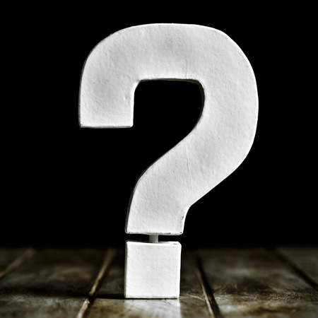 a white three-dimensional question mark on a rustic wooden surface against a black background