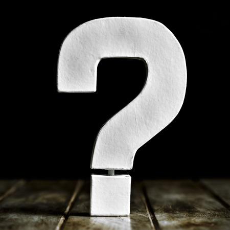 interrogativa: un signo de interrogaci�n tridimensional blanco sobre una superficie de madera r�stica contra un fondo negro