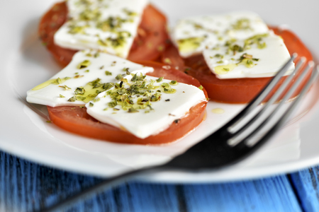 tomato slices: closeup of a white ceramic plate with some slices of tomato topped with fresh cheese and dressed with olive oil and oregano, placed on a rustic blue wooden table Stock Photo