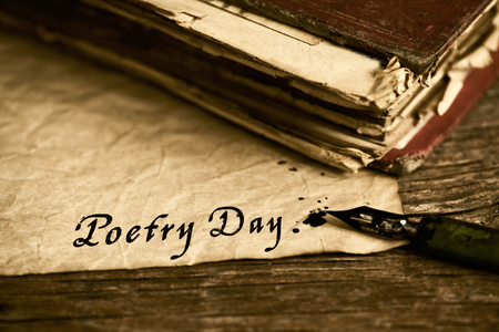 closeup of an old book, an old dip pen and a yellowish paper with the text poetry day written with black ink in it, on a rustic wooden table