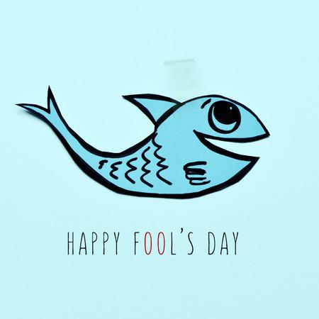 attach: un pez de papel hecho a mano adjunta con cinta adhesiva y el día feliz de los inocentes de texto sobre un fondo azul Foto de archivo