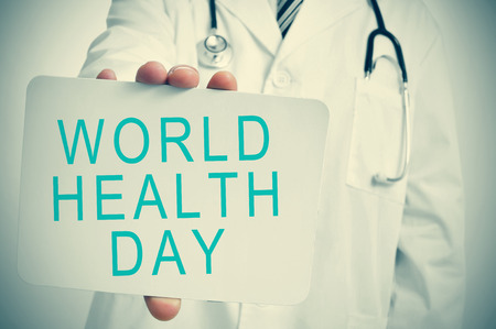 closeup of a young caucasian doctor man showing a signboard with the text world health day Stock Photo