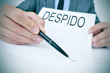 sacked: a young caucasian businessman sitting at his office desk shows a document with the word despido, dismissal written in spanish, and points with a pen the spanish word firma, signature